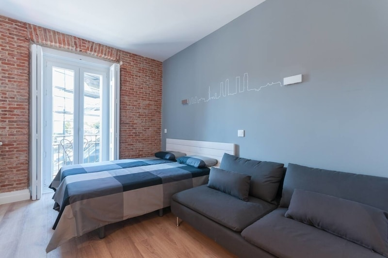 bed and sofa brick faced apartment in Madrid Spain
